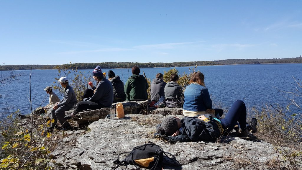A group of students on a weekend trip taking their lunch break near a lake in Missouri.